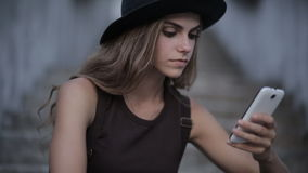 Pretty young girl in a black hat is typing a message on a smartphone stock video footage