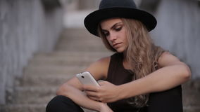 Pretty young girl in a black hat is typing a message on a smartphone stock footage