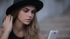 Pretty young girl in a black hat is typing a message on a smartphone stock video
