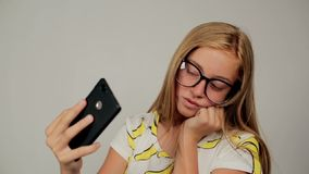 Pretty young girl with blond hair and glasses smiling and taking selfie. Pretty young girl with blond dyed hair smiling and taking selfie while showing two stock video footage