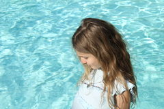 Pretty young girl with blond hair near a pool Stock Photo