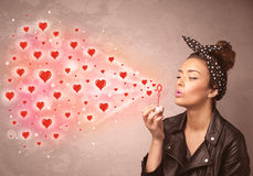 Pretty young girl blowing red heart symbols Royalty Free Stock Photography