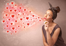 Pretty young girl blowing red heart symbols Stock Image