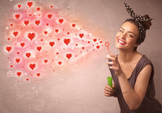Pretty young girl blowing red heart symbols Royalty Free Stock Images