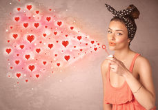 Pretty young girl blowing red heart symbols Stock Photo