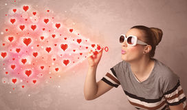 Pretty young girl blowing red heart symbols Royalty Free Stock Photo