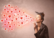 Pretty young girl blowing red heart symbols Royalty Free Stock Photos