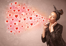 Pretty young girl blowing red heart symbols Stock Photography