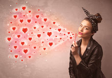 Pretty young girl blowing red heart symbols Stock Images