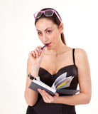 Pretty young girl with book, pen and glasses Royalty Free Stock Image