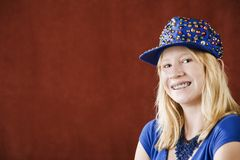 Pretty young girl with braces. Teenage girl with braces wearing a hat with sequins Royalty Free Stock Images