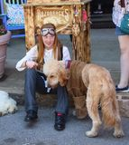 Pretty young girl with braces and long red hair with steampunk goggles sits on curb with labradoodle dog dressed in leather coat a royalty free stock image
