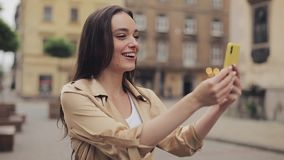 Pretty Young Girl with Brown Hair Wearing Beige Trench Having a Video Call on her Smartphone Smiling and Waving Hand at. City Background stock video