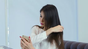 Pretty young girl brushing her hair using phone as a mirror stock video footage