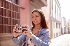 Pretty young girl with a camera looking ahead Stock Image
