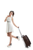 Pretty young girl carries a suitcase on wheels. Funny girl with. Pretty young girl with a bag on wheels. Funny girl with a suitcase in a light white dress Royalty Free Stock Photography