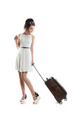 Pretty young girl carries a suitcase on wheels. Funny girl with. Pretty young girl with a bag on wheels. Funny girl with a suitcase in a light white dress Royalty Free Stock Photo