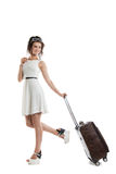 Pretty young girl carries a suitcase on wheels. Funny girl with Stock Image