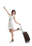 Pretty young girl carries a suitcase on wheels. Funny girl with Stock Photos
