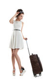 Pretty young girl carries a suitcase on wheels. Funny girl with Stock Photography