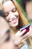 Pretty young girl chatting with smartphone. Portrait of pretty young girl chatting with smartphone royalty free stock photography