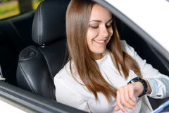 Pretty young girl checking time in car Stock Photo