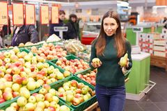 Pretty young girl choosing between ripe pear and apple at market.  Royalty Free Stock Image