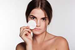 Pretty young girl is cleaning skin with cotton Royalty Free Stock Photos