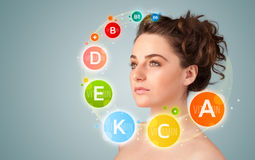 Pretty young girl with colorful vitamin icons and symbols stock image