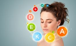 Pretty young girl with colorful vitamin icons and symbols Stock Photos