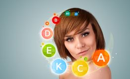 Pretty young girl with colorful vitamin icons and symbols royalty free stock photo