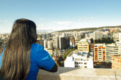 Pretty young girl contemplating the city from a. Pretty young brunette girl contemplating the city from a terrace stock photo