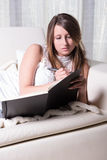 Pretty young girl on couch writing in Book Royalty Free Stock Photo