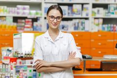 A pretty young girl with dark hair and glasses,wearing a medical overall,stands by the cash desk with her arms crossed stock images