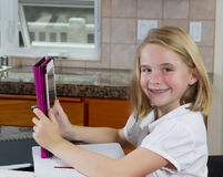 Pretty young girl doing her homework in the kitchen Royalty Free Stock Image