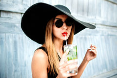 Pretty young girl drink cold coctail outdoor in beach cafe Stock Photo