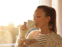 Girl with coffee beside window. Pretty young girl drinking coffee and standing beside window with warm sunshine coming through Stock Photography