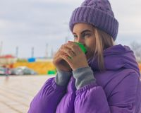Pretty young girl drinks coffee or tea, street Royalty Free Stock Photo