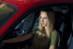 Pretty young girl driving a red sports car royalty free stock photo