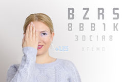 Pretty young girl examining her eyesight Royalty Free Stock Images