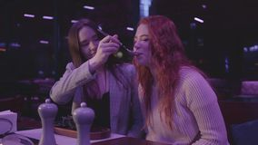Pretty young girl feeding her girlfriend resting in an expensive restaurant. Pretty young girl feeding her girlfriend resting in an expensive restaurant stock footage