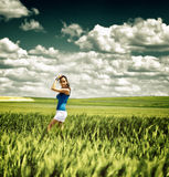Pretty young girl in a field under a dramatic sky stock images