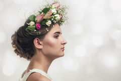 Pretty young girl in a flower wreath of roses Stock Photos