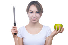 Pretty young girl with green apple and knife Stock Images