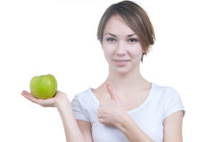 Pretty young girl with green apple showing ok Royalty Free Stock Photos