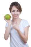 Pretty young girl with green apple showing ok Royalty Free Stock Image