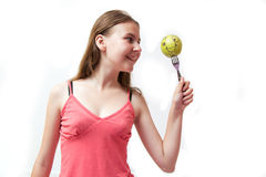 Pretty young girl with a green happy apple Royalty Free Stock Photos