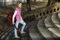 Pretty Young Girl with Guitar in Her Hand Walking Up the Stairs. Pretty Young Girl Casually Dressed with Guitar in Her Hand Walking Up the Stairs in the Park on Royalty Free Stock Image