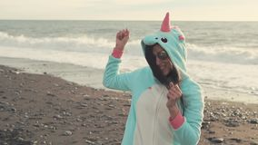 Pretty young girl is having fun on the beach. Happy beautiful girl is dancing and enjoying life on the beach in the evening. She is wearing unicorn kigurumi stock video