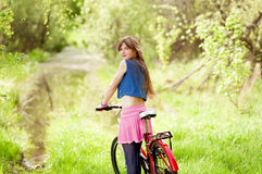 Pretty young girl holding bike. Stock Photography